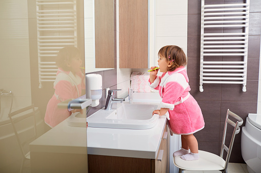 Young patient of The Elmwood Dental Group LLC brushing her teeth in front of mirror in West Hartford, CT